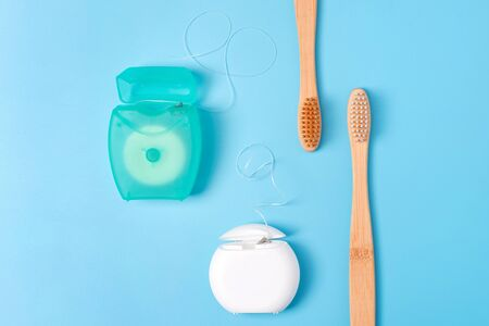 Dental floss containers and bamboo toothbrushes on blue background. Daily oral hygiene, teeth care and health. Cleaning products for mouth. Dental care concept