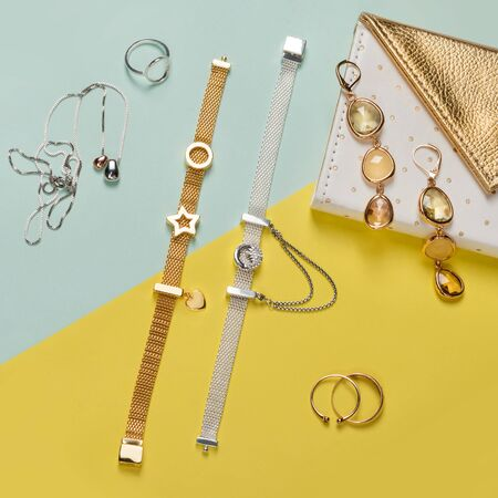 Silver and gold jewelry on minimal yellow and blue background. Rings, bracelets and earrings. Top view of fashion luxury woman accessories, jewelry and shopping concept. Trendy flat lay composition Imagens - 147174352