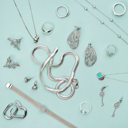 Silver jewelry on minimal mint blue background. Rings, bracelets and earrings. Top view of fashion woman accessories, jewelry and shopping concept. Trendy minimalist geometric flat lay composition