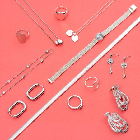 Silver jewelry on minimal pink background. Rings, bracelets and earrings. Top view of fashion woman accessories, jewelry and shopping concept. Trendy minimalist geometric flat lay composition