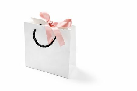 Mock-up of blank craft shopping package, mockup of white paper shopping bag with handles and pink bow on the neutral background. Gift for holiday, shopping and sale concept.