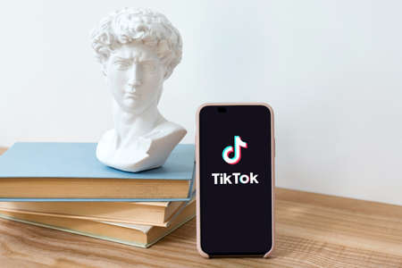 Kyiv, Ukraine - May 28, 2020: TikTok application logo on Iphone X screen on wooden table with books and David head statue. TikTok is a video sharing social networking service. Social media network. Imagens - 148370094