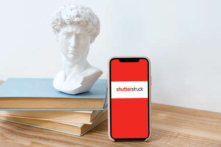 Kyiv, Ukraine - May 28, 2020: Shutterstock logo on Iphone X screen on wooden table with books and David head statue Imagens - 148370095