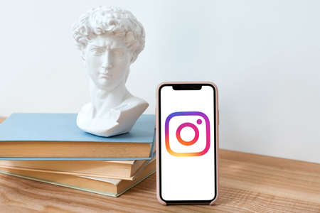Kyiv, Ukraine - May 28, 2020: Instagram logo on Iphone X screen on wooden table with books and David bust statue. Social media network