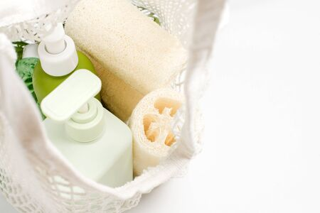 Green container for shampoo, conditioner or liquid soap in eco bag. Loofah or luffa washcloth, vegetable sponge, alternative to plastic, zero waste, eco friendly. Natural beauty products. Imagens - 150070153
