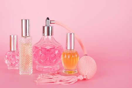 Different transparent perfume bottles on pink background. Aromatic essence bottles. Perfumery, cosmetics, fragrance collection. Free space for text Imagens - 150087391