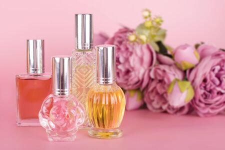 Different transparent perfume bottles with bouquet of peonies on pink background. Aromatic essence bottles with spring flowers. Perfumery, cosmetics, fragrance collection Imagens - 149602993
