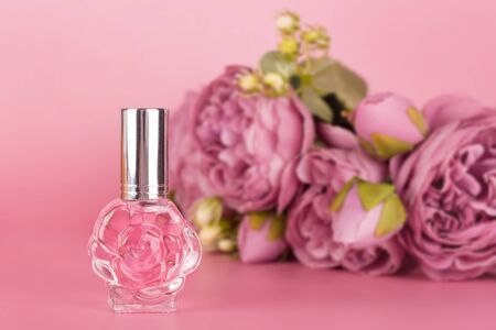 Transparent perfume bottle with bouquet of peonies on pink background. Aromatic essence bottle with spring flowers. Perfumery, cosmetics, fragrance collection. Free space for text.