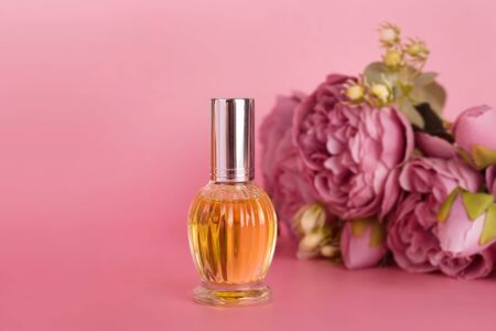 Transparent perfume bottle with bouquet of peonies on pink background. Aromatic essence bottle with spring flowers. Perfumery, cosmetics, fragrance collection. Free space for text. Imagens - 149603579