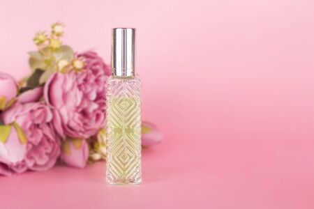 Transparent perfume bottle with bouquet of peonies on pink background. Aromatic essence bottle with spring flowers. Perfumery, cosmetics, fragrance collection. Free space for text. Imagens - 149673410