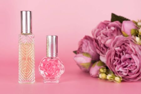 Different transparent perfume bottles with bouquet of peonies on pink background. Aromatic essence bottles with spring flowers. Perfumery, cosmetics, fragrance collection Imagens - 149672961