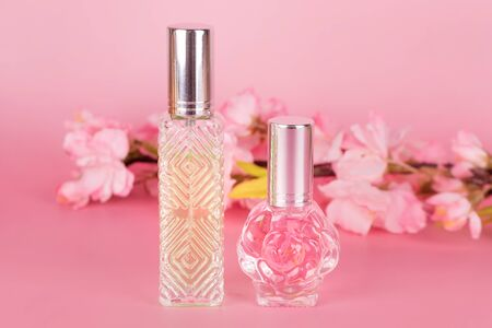 Different transparent perfume bottles with spring blooming tree branch on pink background. Aromatic essence bottles with cherry blossom spring flowers. Perfumery, cosmetics, fragrance collection Imagens - 149673341