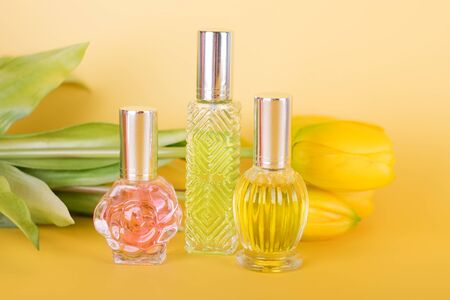 Different transparent perfume bottles with bouquet of tulips on yellow background. Aromatic essence bottles with spring flowers. Perfumery, cosmetics, fragrance collection Imagens - 149673427