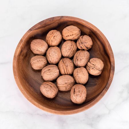 Walnut in wooden bowl on light marble background. Flatlay, top view. Wooden plate with walnuts. Space for text. Organic food, natural foods. Imagens - 150350222