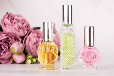 Different transparent perfume bottles with bouquet of peonies on light marble background. Aromatic essence bottles with spring flowers. Perfumery, cosmetics, fragrance collection