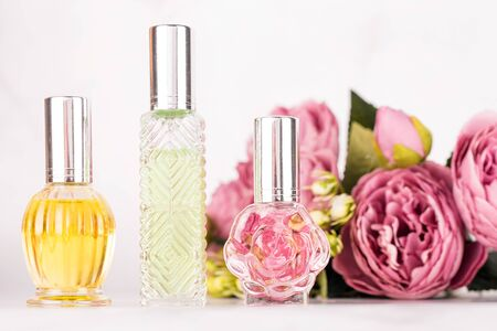 Different transparent perfume bottles with bouquet of peonies on light marble background. Aromatic essence bottles with spring flowers. Perfumery, cosmetics, fragrance collection Imagens - 149925911