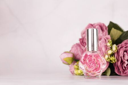Pink transparent perfume bottle with bouquet of peonies on light marble background. Aromatic essence bottle with spring flowers. Perfumery, cosmetics, fragrance collection. Free copyspace. Imagens - 149933369
