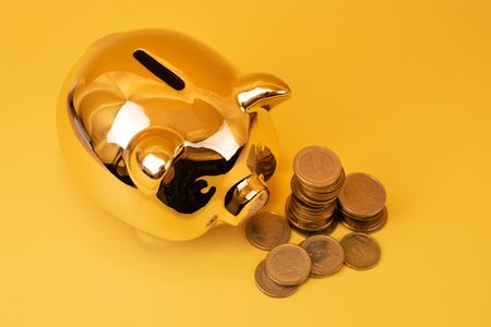 Golden piggy bank with money towers on yellow background. Stack of euro coins near golden money box. Money pig, money saving, moneybox, finance and investments concept. Free space for text. Imagens - 150083534
