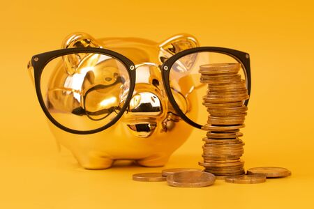 Golden piggy bank wearing glasses with money towers. Stack of euro coins near golden money box. Money pig, money saving, moneybox, pile of coins. Finance and investments. Free space for text. Imagens - 150090461