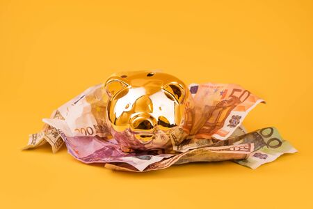 Golden piggy bank with cash money, euro and dollar banknotes. Golden money box, huge savings, money accumulation. Money saving, moneybox, finance and investments, budget concept. Copyspace. Imagens - 150431650