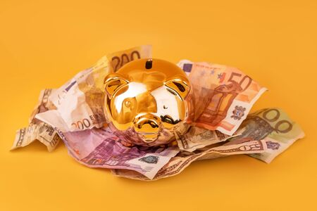 Golden piggy bank with cash money, euro and dollar banknotes. Golden money box, huge savings, money accumulation. Money saving, moneybox, finance and investments, budget concept. Copyspace. Imagens - 150431652