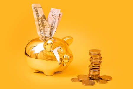 Golden piggy bank with money tower and dollar bills on yellow background. Stack of euro coins near golden money box. Money pig, money saving, moneybox, finance and investments concept