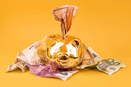 Golden piggy bank with cash money, euro and dollar banknotes. Golden money box, huge savings, money accumulation. Money saving, moneybox, finance and investments, budget concept. Copyspace.