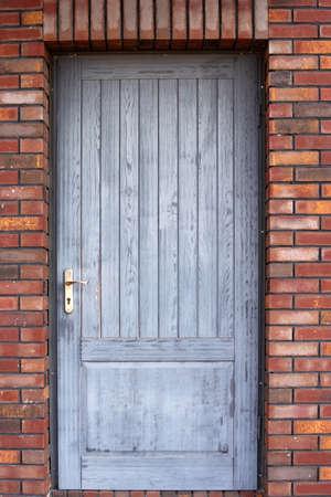 Old wooden front door of a red brick house Stock fotó