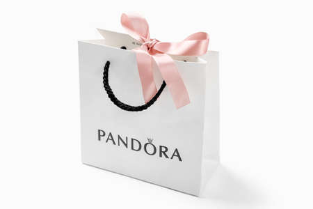 KYIV, UKRAINE - MAY 21, 2020: Pandora paper bag with pink bow on white table. Famous for its bracelets with golden and silver charms brand is a manufacturer of jewelry products in Copenhagen, Denmark.