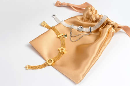 KYIV, UKRAINE - MAY 21, 2020: Pandora gift bag with bracelets from new reflections collection on white table. Golden and silver charms, famous jewelry products manufactured in Copenhagen, Denmark. Sajtókép