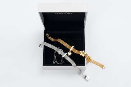 KYIV, UKRAINE - MAY 21, 2020: Pandora gift box with bracelets from new reflections collection on white table. Golden and silver charms, famous jewelry products manufactured in Copenhagen, Denmark.