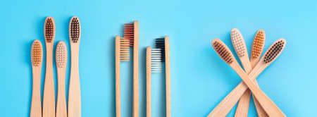 Bamboo toothbrushes on blue background. Eco friendly daily oral hygiene, teeth care and health. Banner with cleaning products for mouth. Dental care concept. Stock fotó