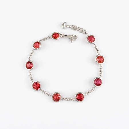 White gold or silver bracelet with red ruby gemstone on light background.