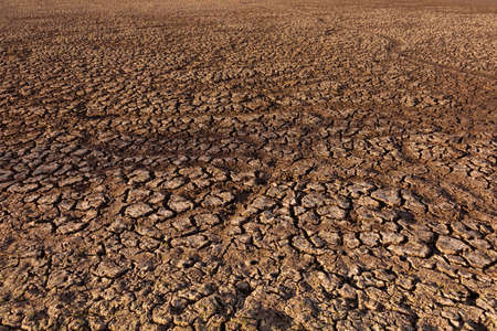 Cracked and dry earth in the desert Global warming and shortage of water on the planet concept. Drought, cracked ground. Natural texture of soil with cracks, wasteland. Stock Photo