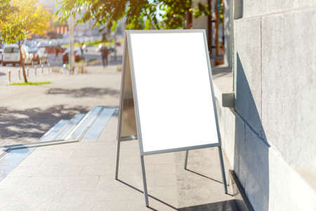 Signboard on the street. Angled empty menu board stand. Restaurant sidewalk white sign board. Freestanding A-frame advertising board near outdoor cafe. Selective focus Imagens