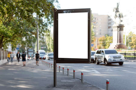 Blank mock up of vertical street poster billboard on city background. Blanck billboard for advertising on the sidewalk next to the road. Imagens