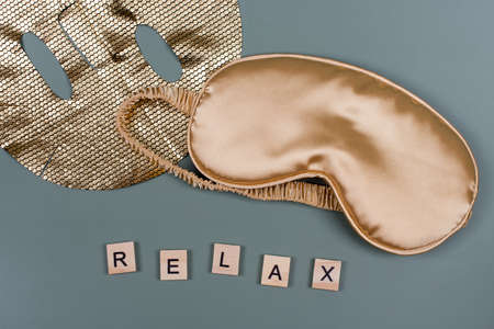 Word RELAX with golden sleeping eye mask and cosmetic facial sheet mask. Good night, flight and travel concept. Sweet dreams, relax, siesta, insomnia, relaxation, beauty spa and wellness concept.