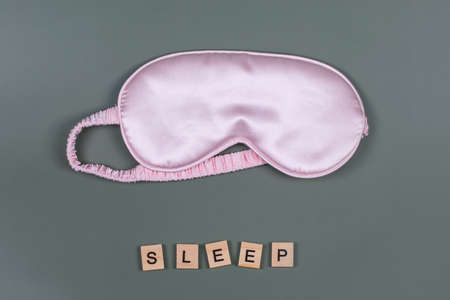 Word SLEEP and pink sleeping eye mask, top view. Good night, flight and travel concept. Sweet dreams, relax, siesta, insomnia, relaxation, tired, travel concept. Do not disturb, bedtime concept