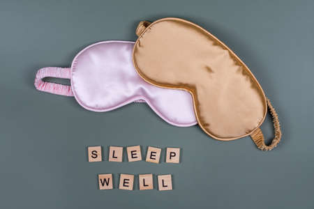 Words SLEEP WELL and sleeping eye masks, top view. Good night, flight and travel concept. Sweet dreams, relax, siesta, insomnia, relaxation, tired, travel concept. Do not disturb, bedtime concept