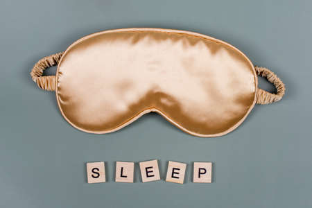 Word SLEEP and golden sleeping eye mask, top view. Good night, flight and travel concept. Sweet dreams, relax, siesta, insomnia, relaxation, tired, travel concept. Do not disturb, bedtime concept