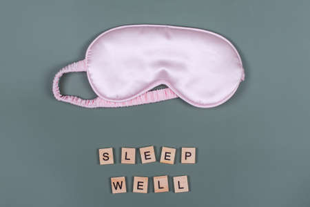 Words SLEEP WELL and pink sleeping eye mask, top view. Good night, flight and travel concept. Sweet dreams, relax, siesta, insomnia, relaxation, tired, travel concept. Do not disturb, bedtime concept Imagens