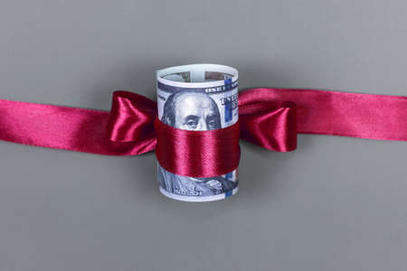 Hundred dollar bill tied with red bow on grey background. Money, gift wrapped in red bow and ribbon, US currency, cash, business success, bonus, monetary prize, luck in the game concept Imagens