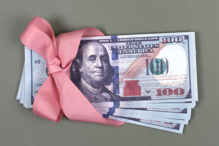 Hundred dollar bill tied with pink bow on grey background. Money, gift wrapped in pink bow and ribbon, US currency, cash, business success, bonus, monetary prize, luck in the game concept.