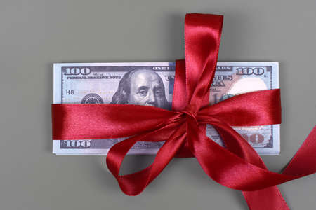 Money as gift concept, win or bonus, hundred dollar bills on grey background. Pile of 100 dollar bills is tied with red ribbon with bow.