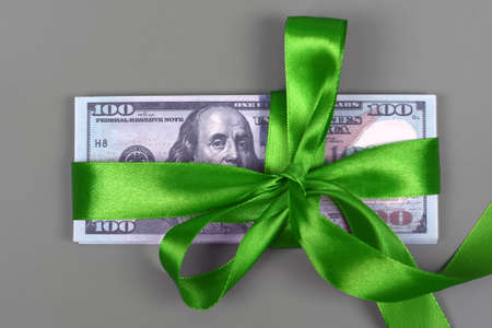 Hundred dollar bill tied with green bow on grey background. Money, gift wrapped in green bow and ribbon, US currency, cash, business success, bonus, monetary prize, luck in the game concept