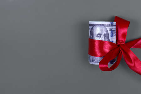 Money as gift concept, win or bonus, hundred dollar bills on grey background. Rolled 100 dollar bills is tied with red ribbon with bow. Copyspace for text.