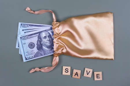 Money in golden gift bag with word SAVE. Saving investing concept. American currency, cash, bonus, monetary prize, pile of 100 dollar bills