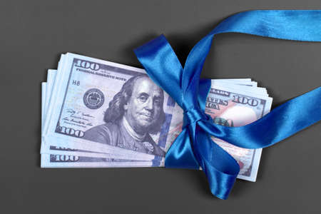 Money as gift concept, win or bonus, hundred dollar bills on grey background. Pile of 100 dollar bills is tied with blue ribbon with bow.