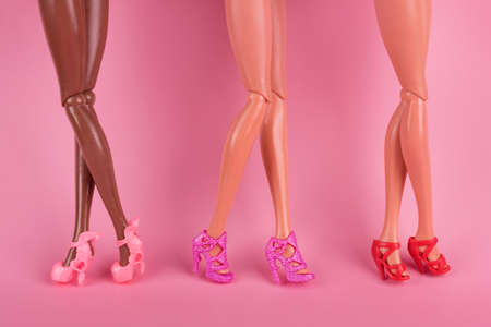 Long skinny legs of a plastic toy dolls in stylish heel shoes. Legs of dolls representing different races on pink background. The concept of female friendship, fashion and beauty.