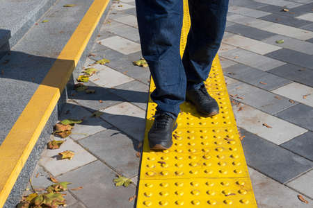 Man walking on yellow blocks of tactile paving for blind handicap. Braille blocks, tactile tiles for the visually impaired, Tenji blocks.Textured ground surface indicators located on sidewalks, stairs